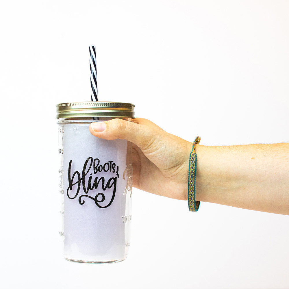 "24 oz reusable glass mason jar tumbler with a gold straw lid and a black and white stripped reusable straw. Text on the jar says ""boots & bling"" in black cursive text"