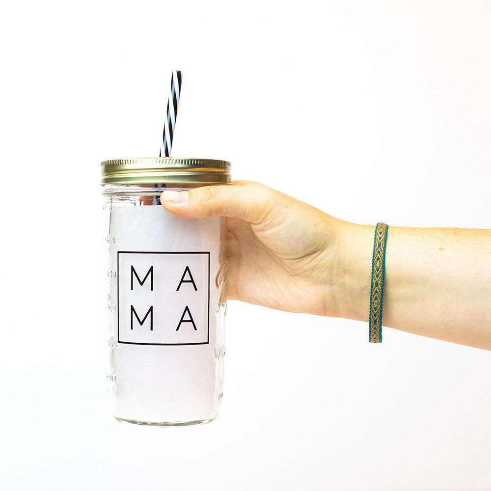 "24 oz reusable glass mason jar tumbler with a gold straw lid and a black and white stripped reusable straw. on the jar is the word ""Mama"" in black thin text with a black square surrounding it."
