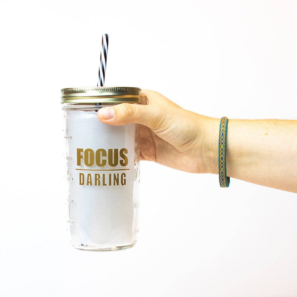 "24 oz reusable glass mason jar tumbler with gold straw lid and a black and white stripped reusable straw. The text on the jar says ""FOCUS"" in thick block text with a line underneath, and then ""DARLING"" in think block text. All text is in gold"