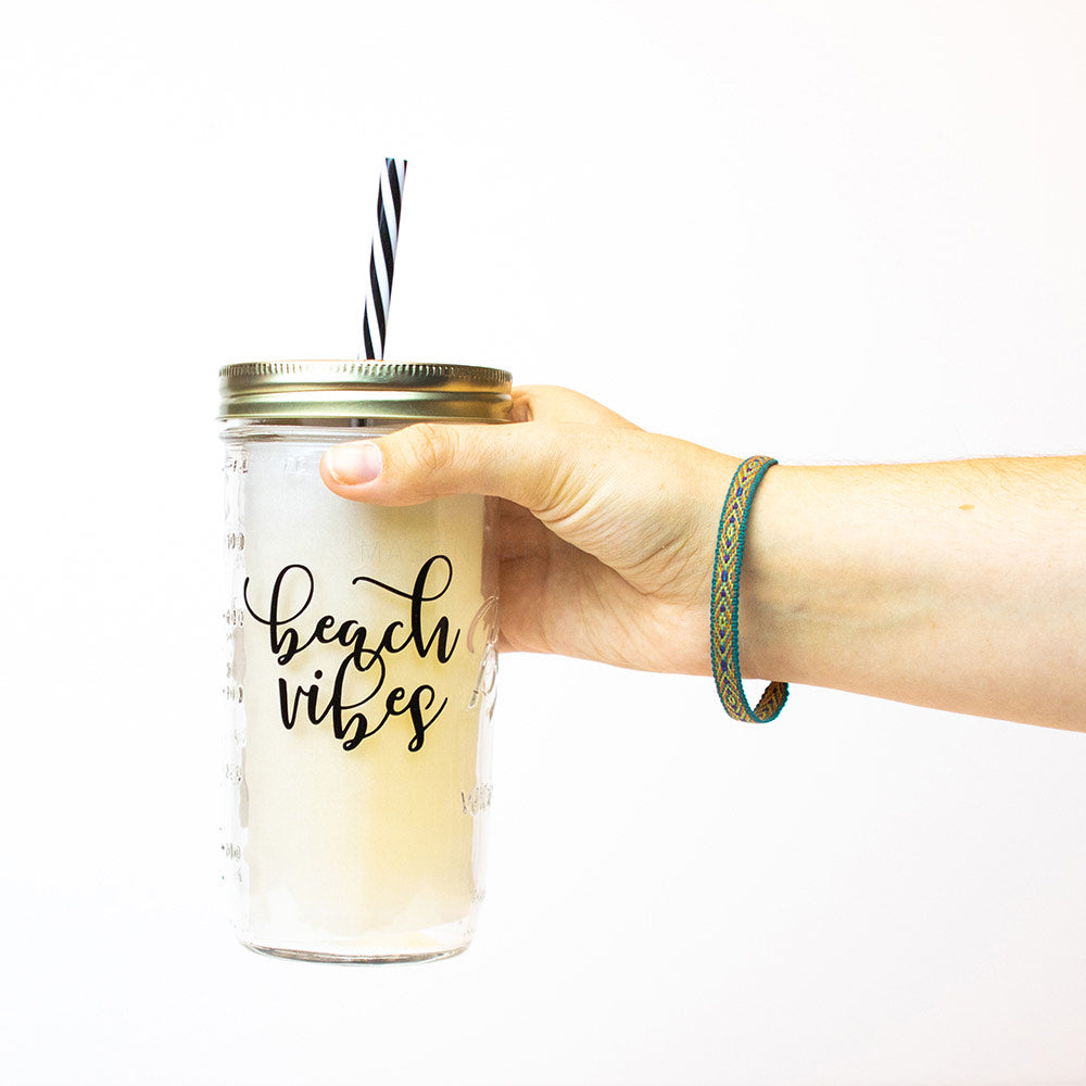 "24 oz reusable glass mason jar tumbler with a gold straw lid and a black & white stripped reusable straw. Text on jar says ""beach vibes"" in black cursive text"