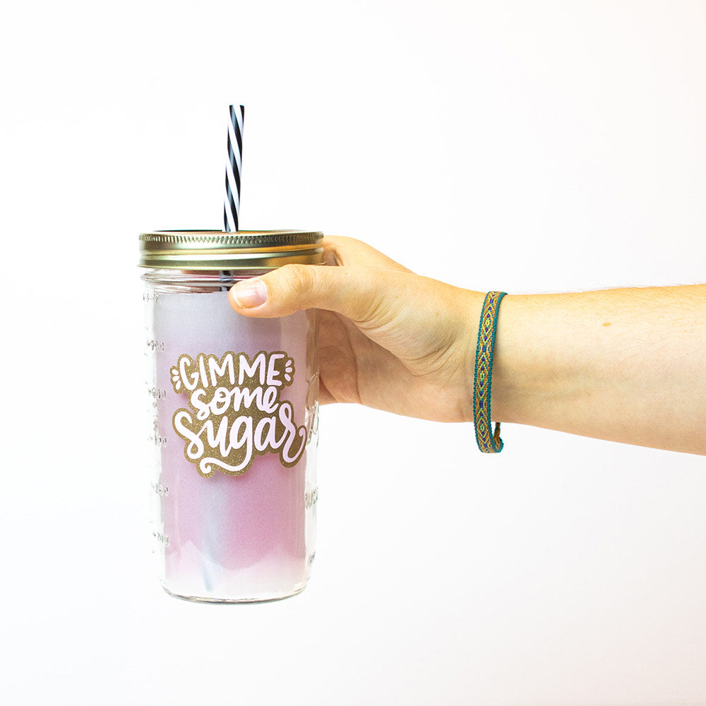 "24 oz reusable glass mason jar tumbler with gold straw lid and a black and white stripped reusable straw. Text on jar says ""GIMME some Sugar"" in white text with gold sparkles surrounding it"