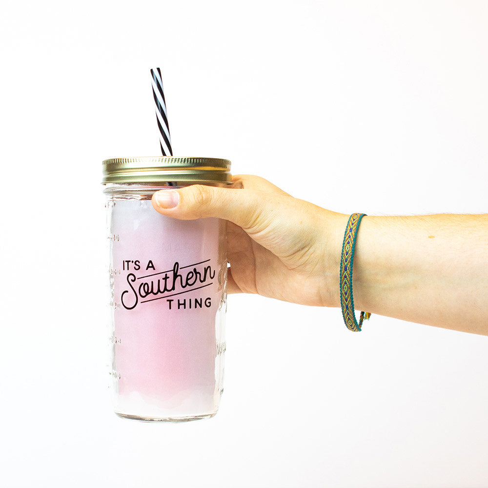 "A hand holds a 24 oz reusable glass mason jar tumbler with a gold straw lid and a reusable black and white stripped straw. On the jar are the words ""ITS A Southern THING"" in block text and cursive."