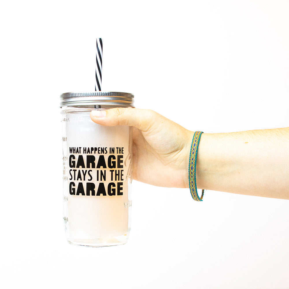 "A hand holds a 24 oz glass reusable mason jar tumbler with a silver straw lid and a black and white stripped reusable straw. On the jar are the words ""what happens in the garage stays in the garage"" in black text"