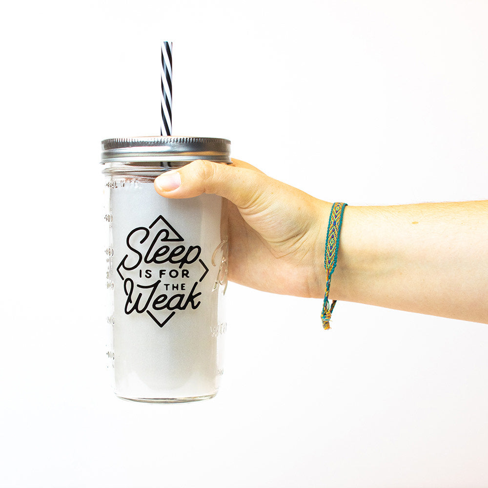 "A hand holds a 24 oz glass reusable mason jar tumbler with a silver straw lid and a black and white stripped reusable straw. On the jar is a black diamond shaped box with the words ""sleep is for the weak"" inside in black text"