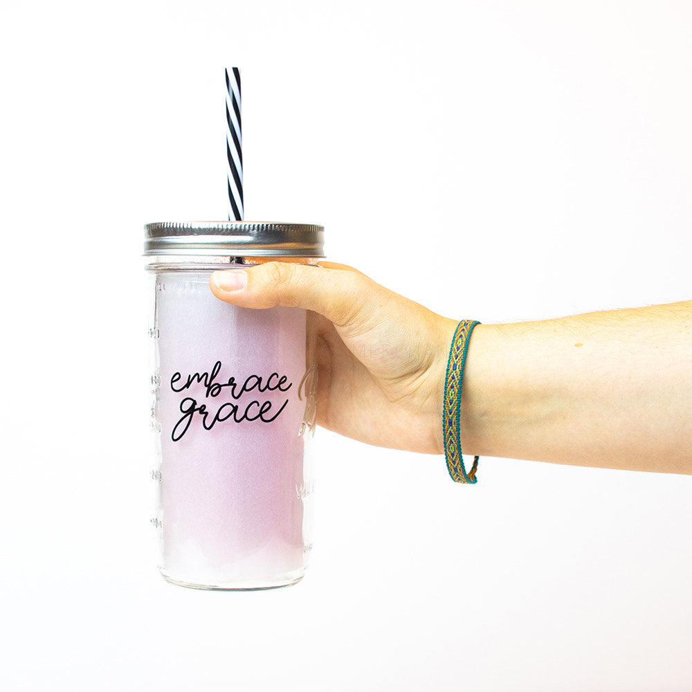 "A hand holds a 24 oz reusable glass mason jar tumbler with silver straw lid and a black and white stripped reusable straw. The text on the jar says ""embrace grace"" in thin black cursive."