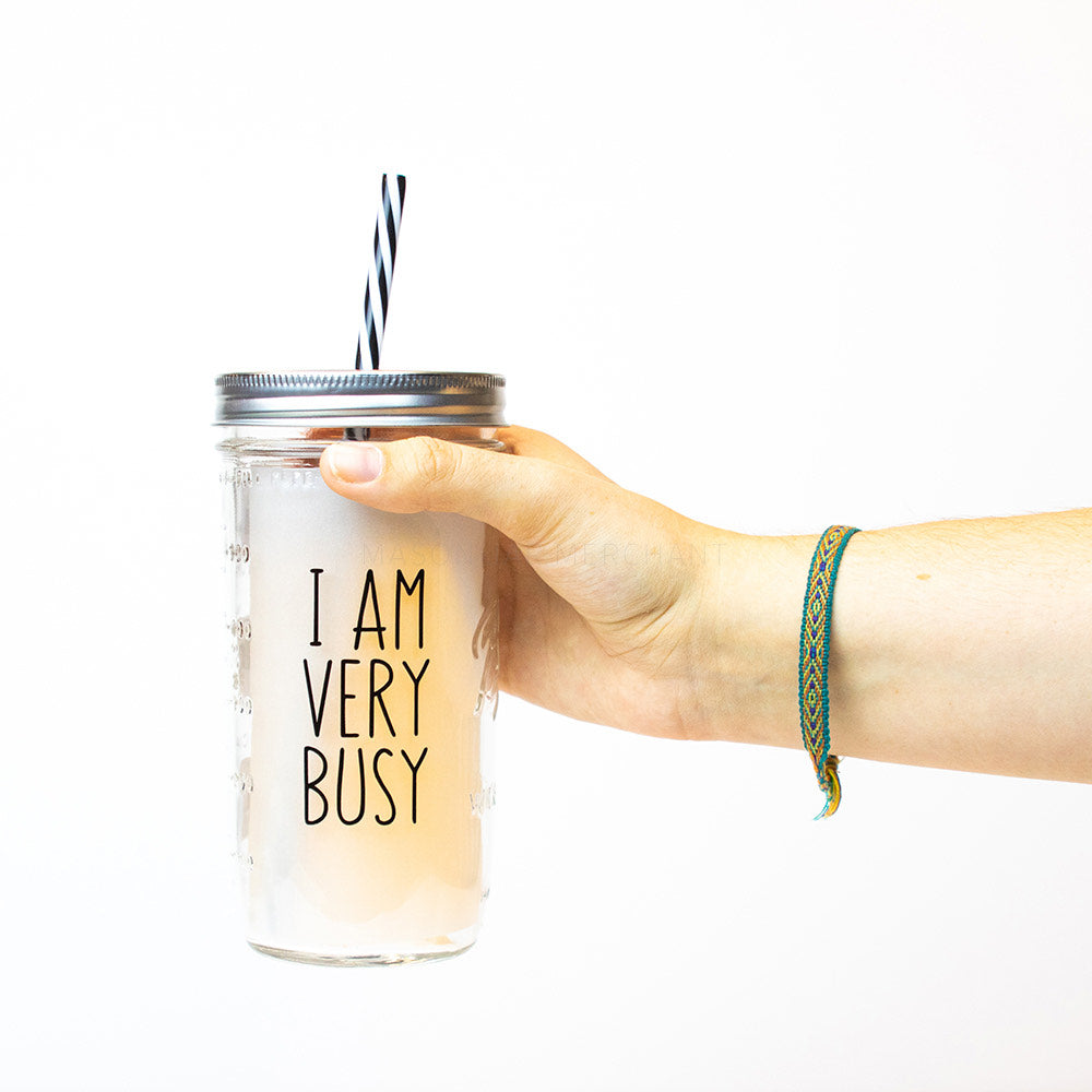"Hand holding a 24 oz Mason Jar tumbler with silver lid and black and white straw that reads ""I ""am very busy"" in black, on a white background"