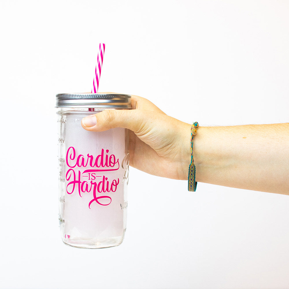 "A hand holds a 24 oz reusable glass mason jar tumbler with silver straw lid and a pink and white stripped reusable straw. The words ""Cardio IS Hardio"" are written on the jar in hot pint cursive letters"