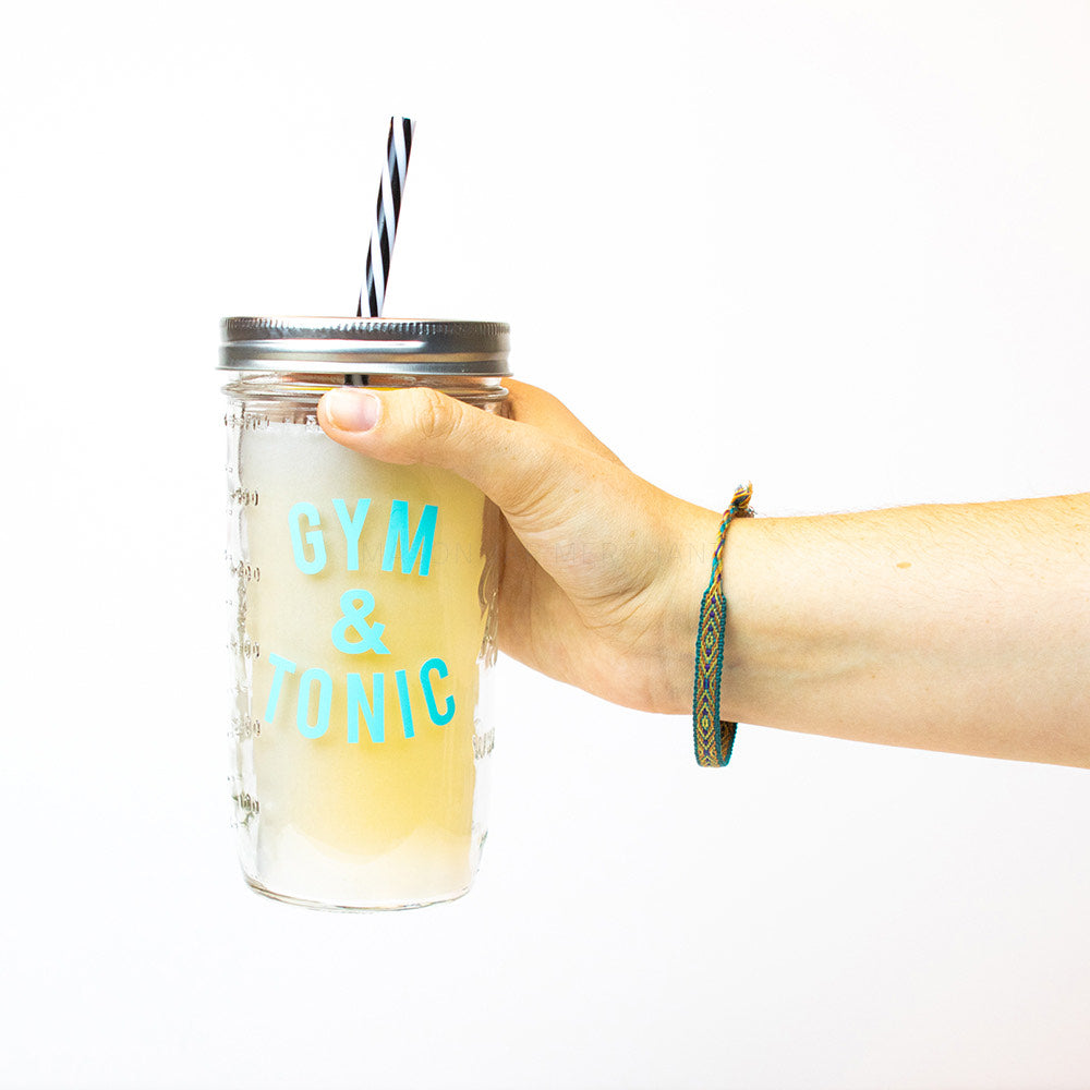 "Hand holding a 24 oz Mason Jar tumbler with silver lid and black and white straw that reads ""Gym & Tonic"" in aqua, on a white background"