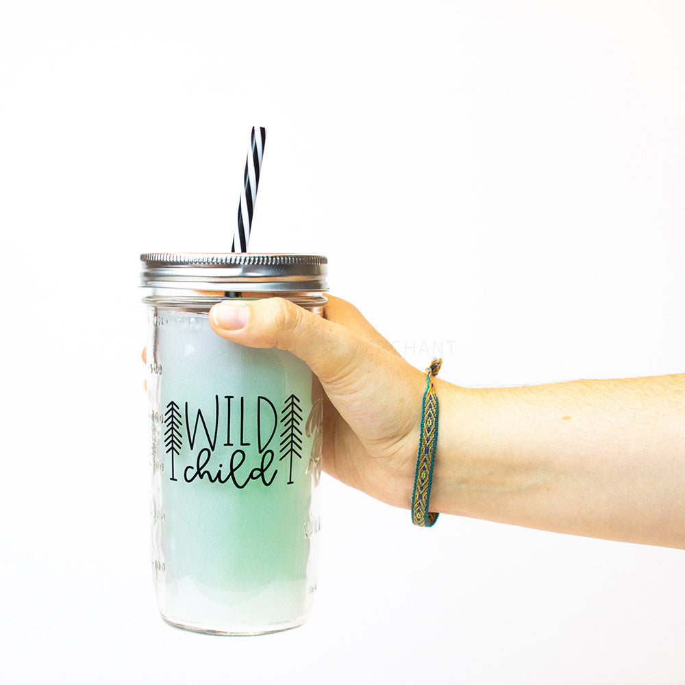 "A hand holds a 24 oz glass reusable mason jar tumbler with a silver straw lid and a black and white reusable straw. On the jar are the words ""Wild Child"" in black text. On each side of the text is a black stick tree"
