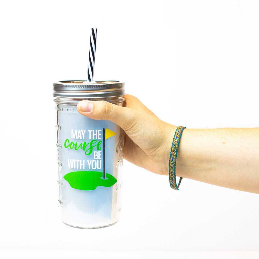 "24 oz reusable glass mason jar tumbler with a silver straw lid and a black and white stripped reusable straw. On the jar is a picture of a golfing putt and the words ""may the course be with you"" in white and green text"
