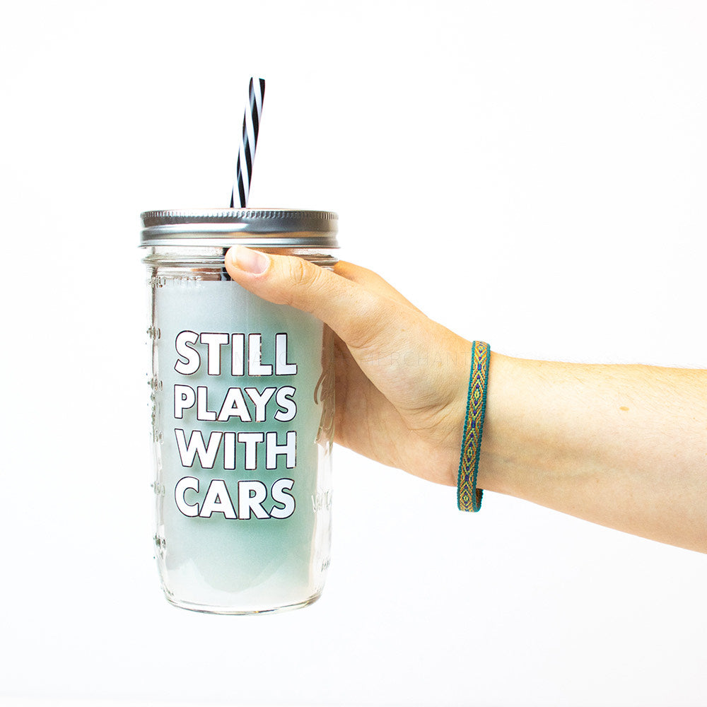 "A hand holds a 24 oz glass reusable mason jar with  a silver straw lid and a black and white stripped reusable straw. On the jar are the words ""Sill plays with cars"" in white block text"""