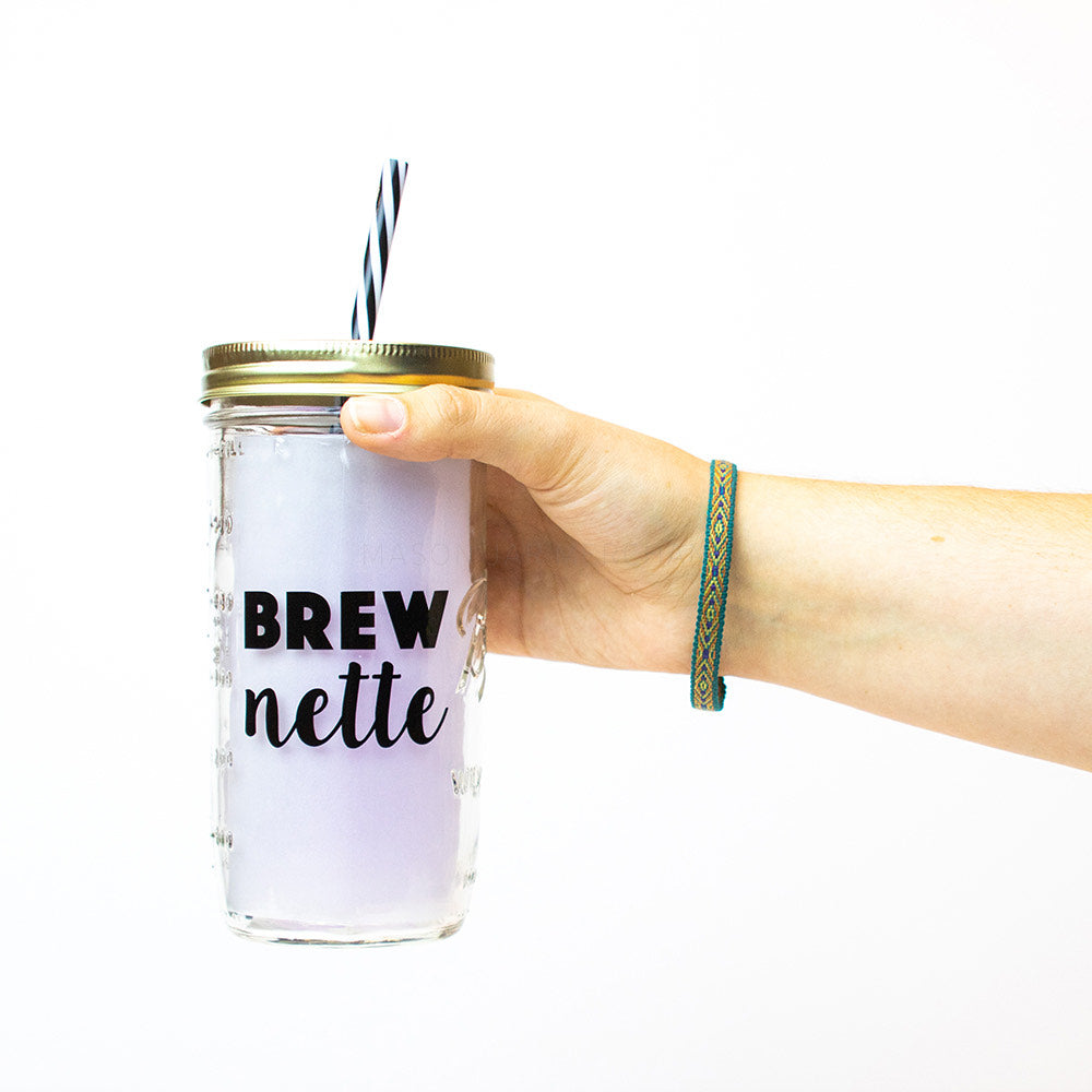 "24 oz reusable glass mason jar tumbler with a gold lid and a black and white stripped reusable straw. Text on the jar is in black and says ""BREW"" on the top in thick block text and ""nette"" below that in thick cursive text"