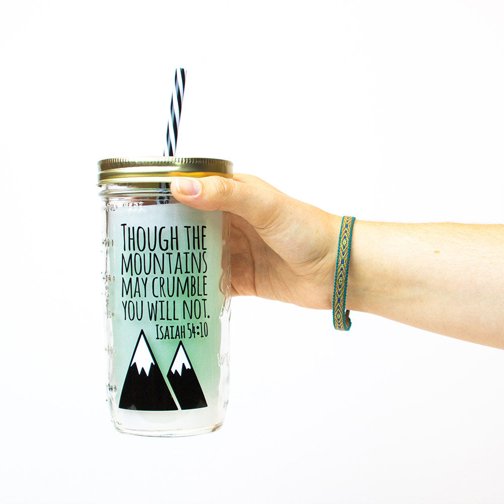 "24 oz glass reusable mason jar tumbler with a gold straw lid and a black and white stripped reusable straw. on the jar are the words ""though the mountains may crumble you will not Isaiah 54:10"" in black text. Underneath the text are two black snow-capped mountains"