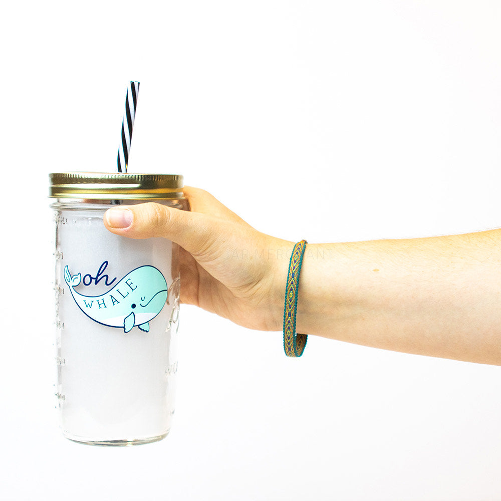 "A hand holds a24 oz reusable glass mason jar tumbler with a gold straw lid and a black and white stripped reusable straw. On the jar is a blue whale with the word ""Whale"" in blue in it and the word ""Oh"" above it in dark blue"