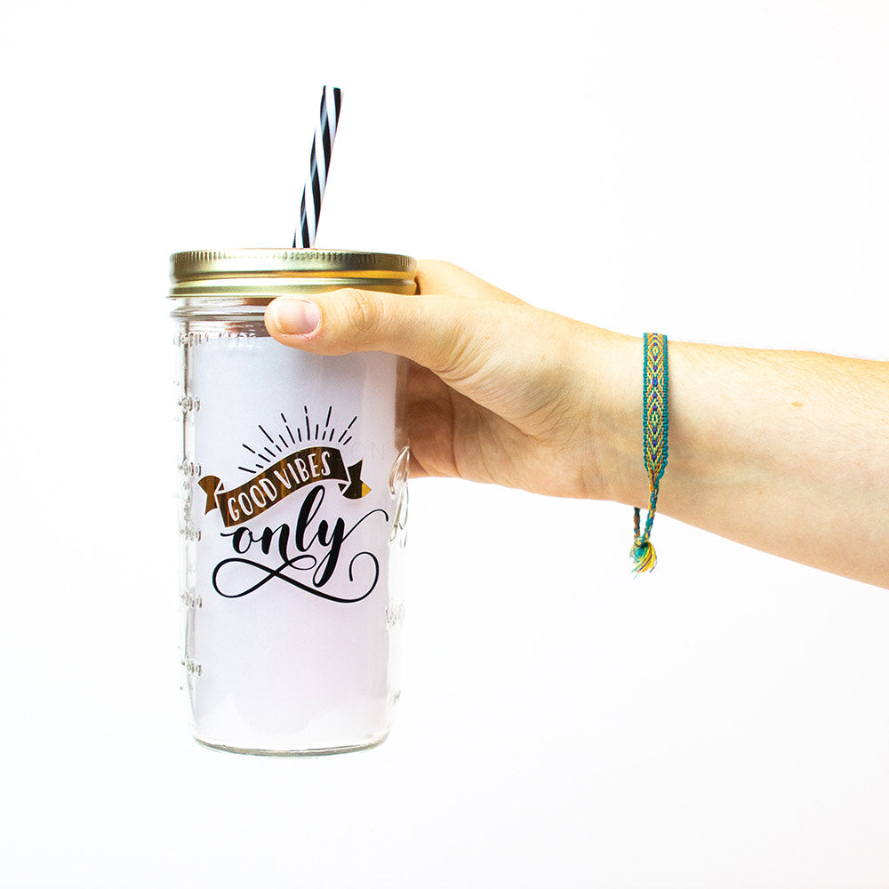 "Hand holding a 24 oz Mason Jar tumbler that reads ""Good vibes only"" in black and chrome"