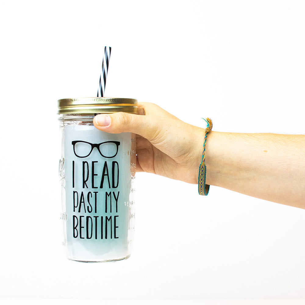 "Hand holding a 24 oz Mason Jar tumbler with gold lid and black and white straw that reads ""I read past my bedtime"" in black, on a white background"