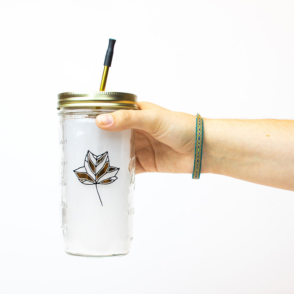 a hand holds a 24 oz glass reusable mason jar tumbler with gold straw lid and a gold metal reusable straw. On the jar is a black and gold botanical leaf