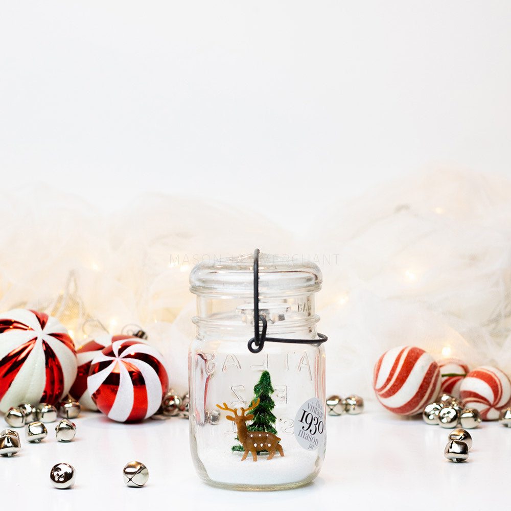 A snowy green tree scene with a small deer in a vintage mason jar pint sitting on a white background with red and white Christmas balls and silver jingle bells