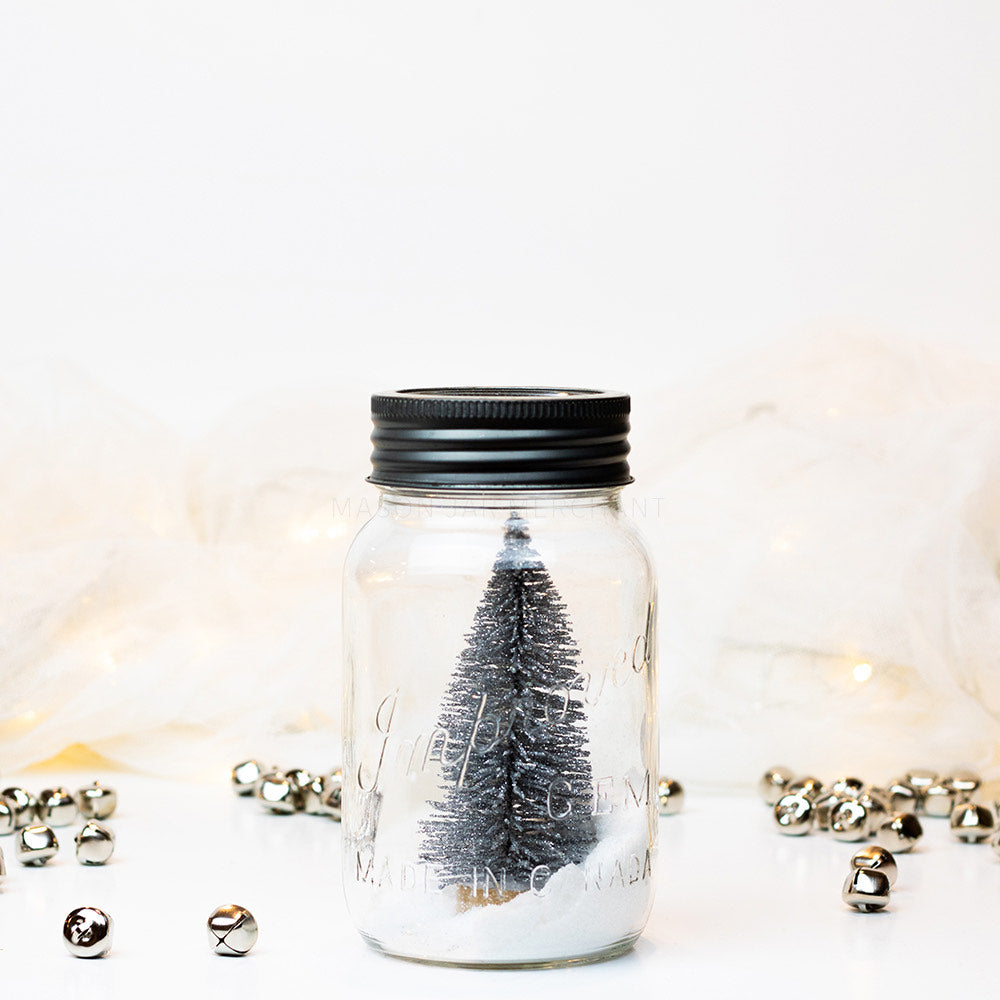 A snowy silver tree scene in a vintage gem quart sitting on a white background with silver jingle bells