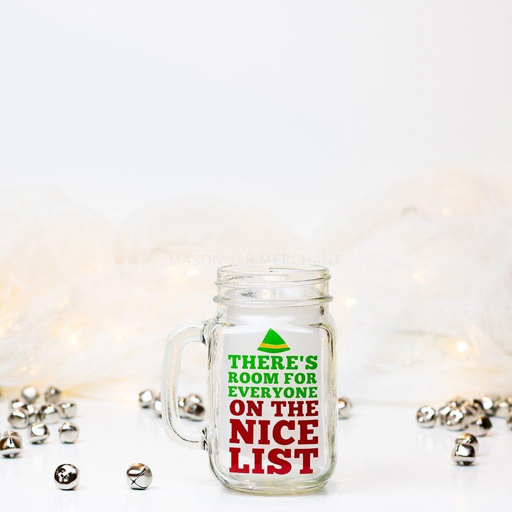 "16 oz glass reusable mason jar tumbler sits on a white background with jingle bells on the counter. On the jar is a green elf hat and then the words ""there's room for everyone"" in green and ""on the nice list"" in red underneath"
