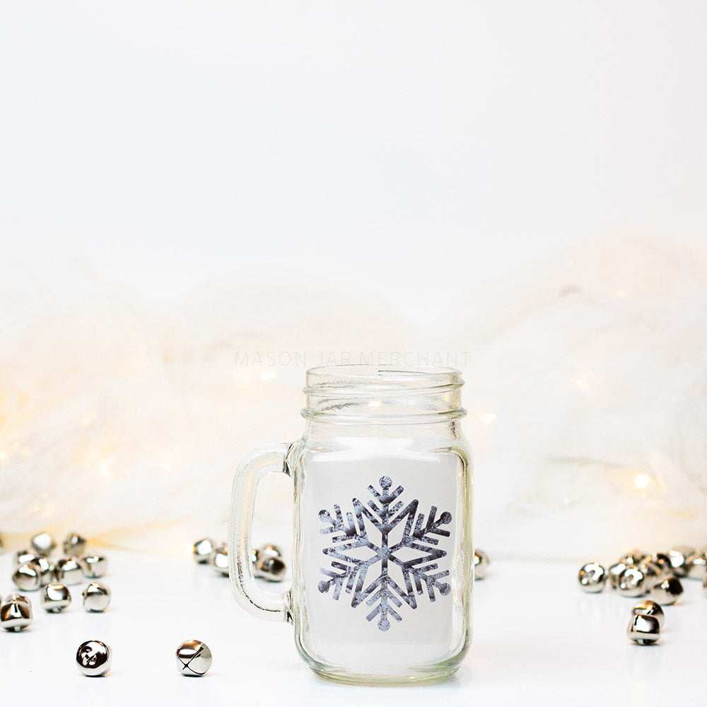 A 16 oz glass reusable mason jar mug sits on a white background with jingle bells on the counter. On the mug is a silver sparkly snowflake