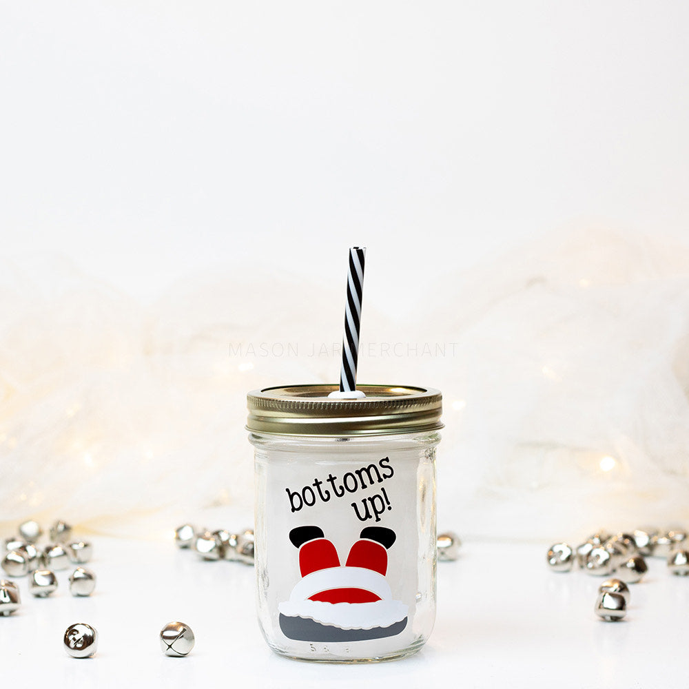 "16 oz reusable glass mason jar tumbler with a gold straw lid and a black and white stripped reusable straw. Text on the jar says ""bottoms up!"" on a slant above an upside down Santa with his head in a chimney"