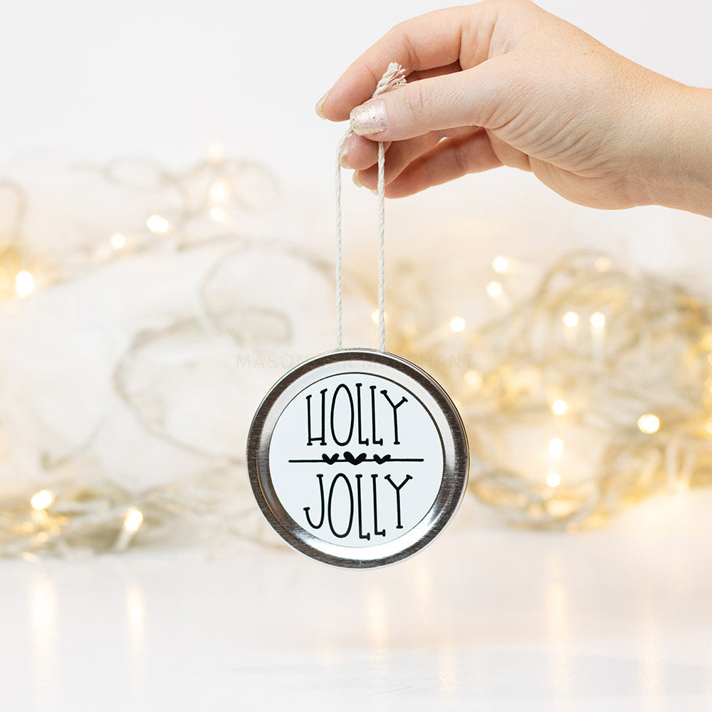 "A hand holds a silver mason jar lid Christmas ornament that says ""Holly Jolly"" in black text on a white background. In the background of the picture are white Christmas lights"