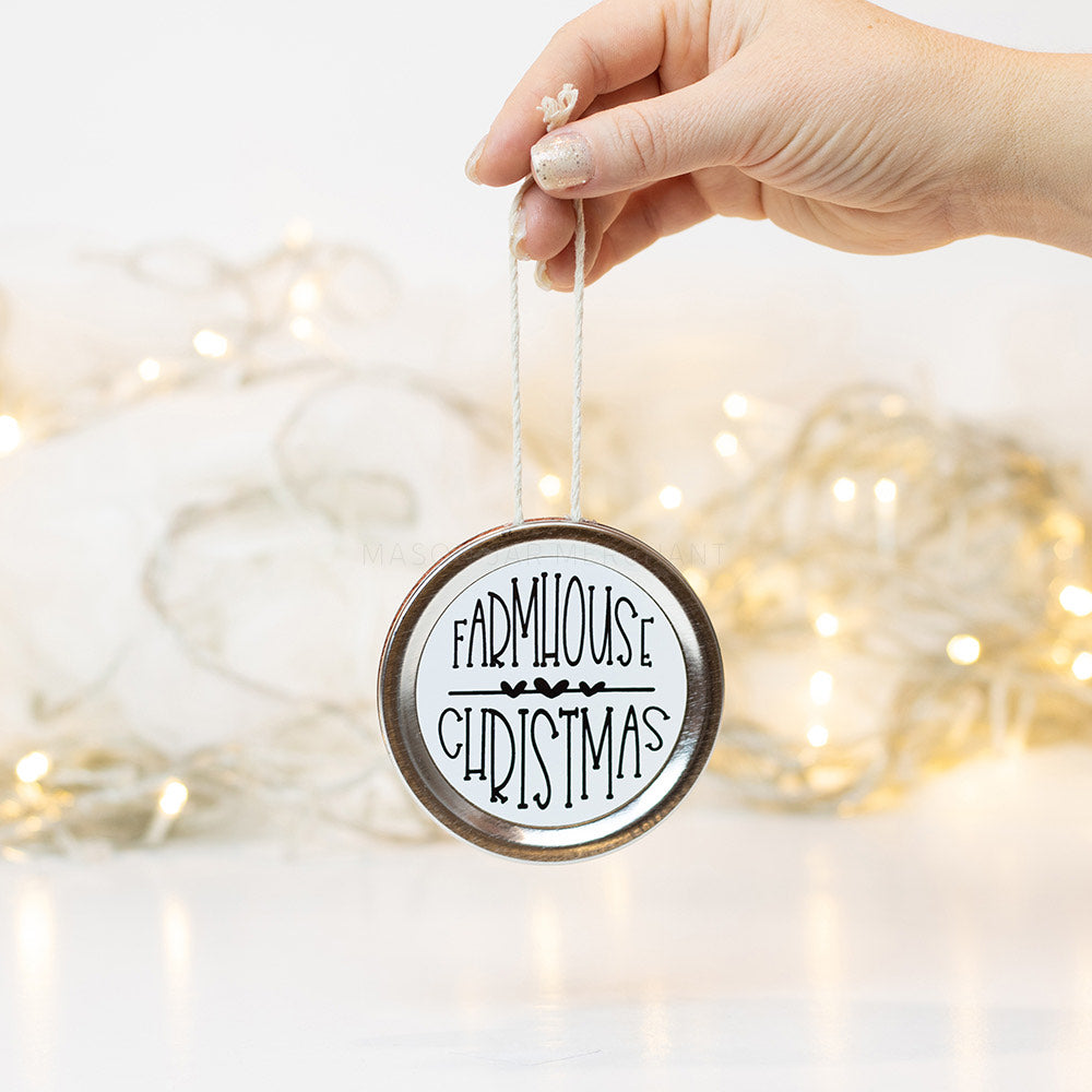 "A hand holds a silver mason jar lid Christmas ornament that says ""Farmhouse Christmas"" in black text on a white background. In the background of the picture are white Christmas lights"