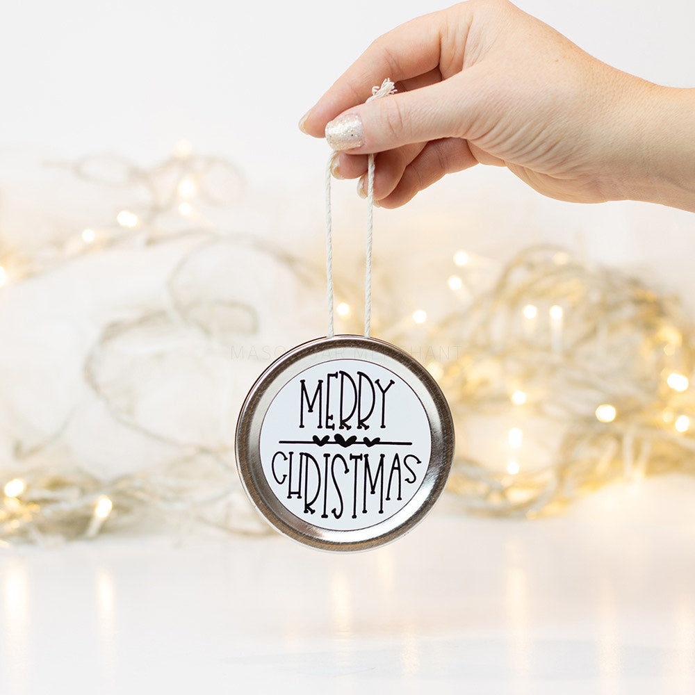 "A hand holds a silver  mason jar lid Christmas ornament that says ""Merry Christmas"" in black text on a white background. In the background of the picture are white Christmas lights"