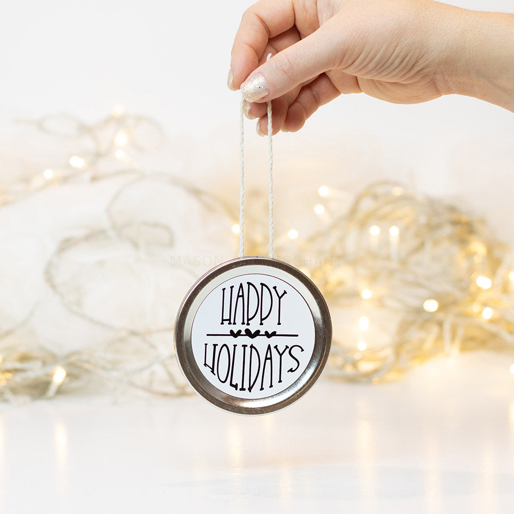"A hand holds a silver mason jar lid Christmas ornament that says ""Happy Holidays"" in black text on a white background. In the background of the picture are white Christmas lights"