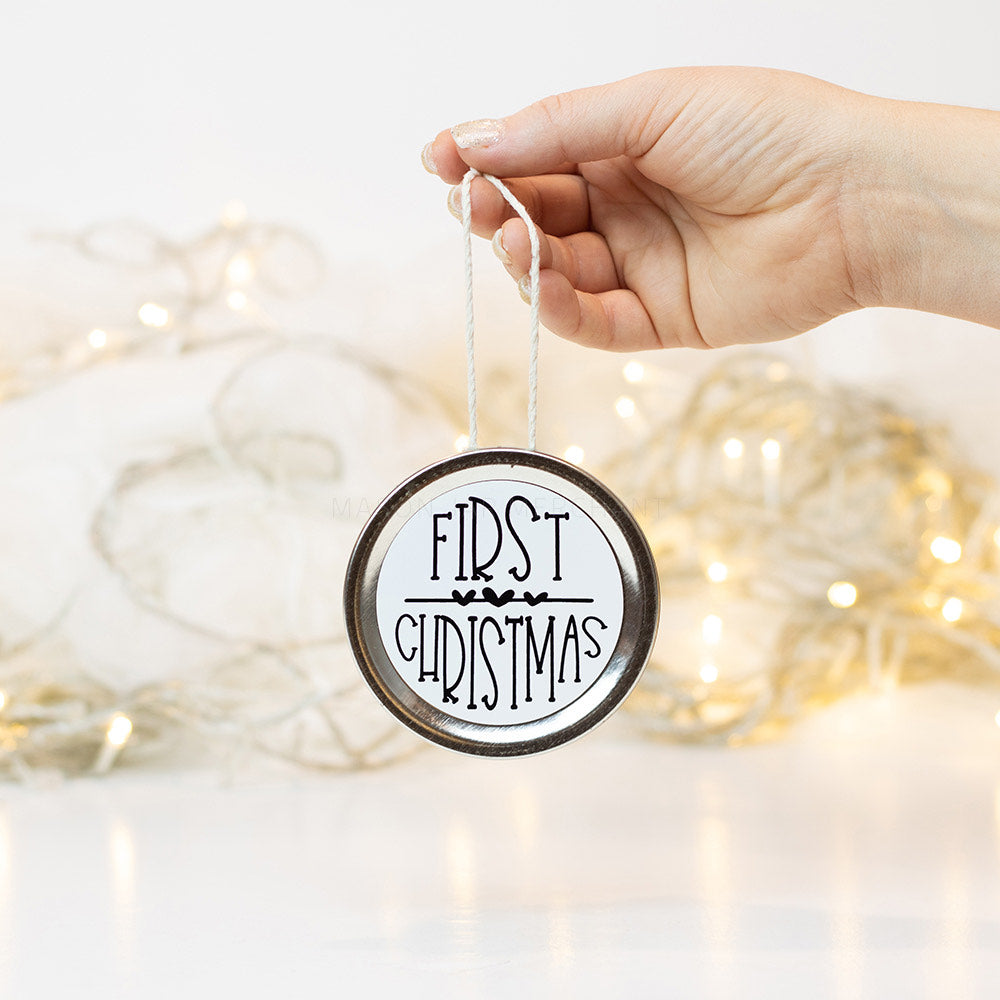"A hand holds a silver mason jar lid Christmas ornament that says ""First Christmas"" in black text on a white background. In the background of the picture are white Christmas lights"