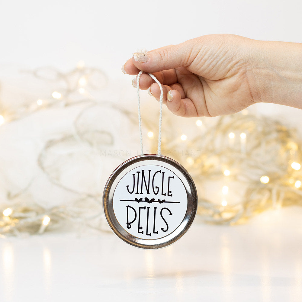 "A hand holds a silver mason jar lid Christmas ornament that says ""Jingle Bells"" in black text on a white background. In the background of the picture are white Christmas lights"