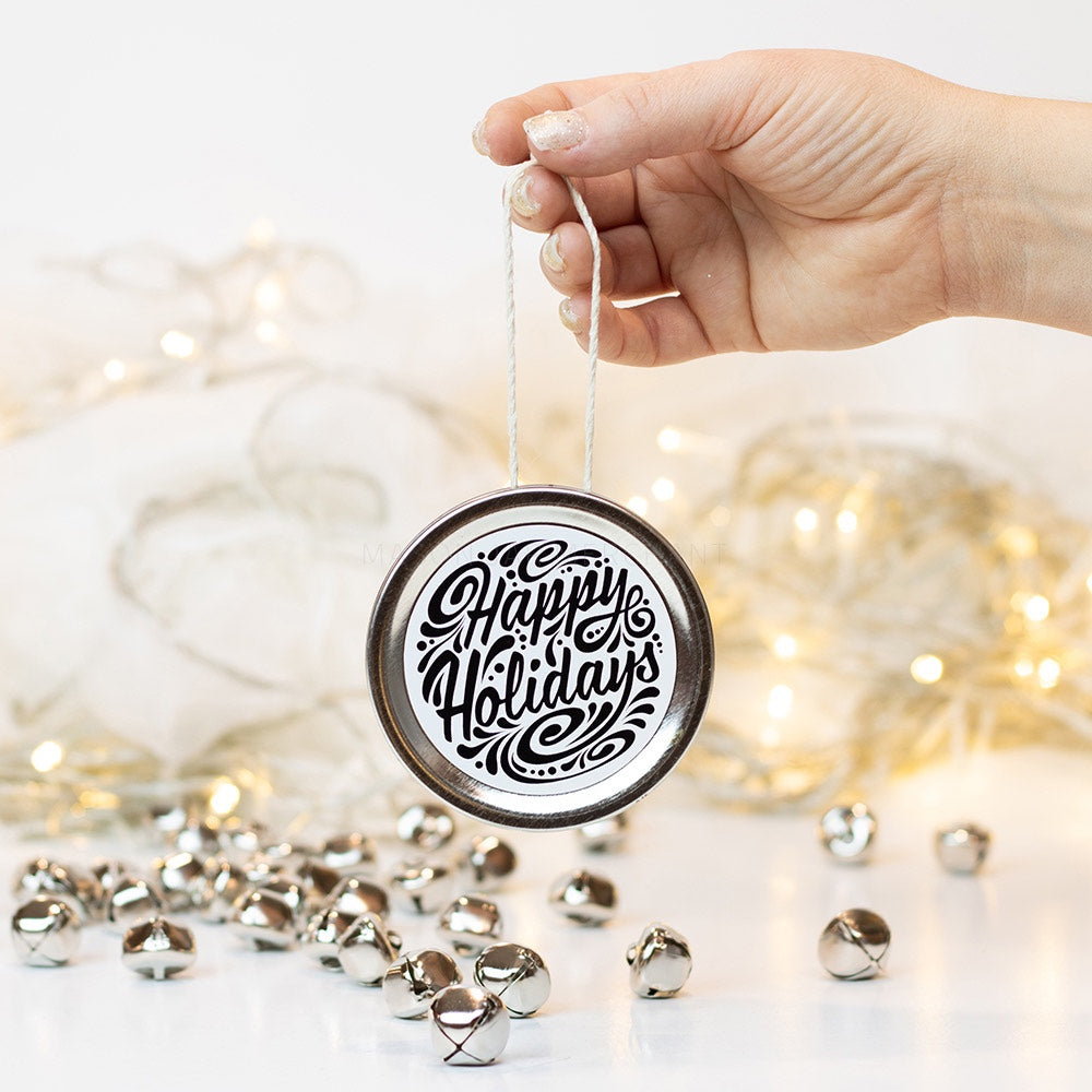 "A hand holds a silver mason jar lid Christmas ornament that says ""Happy Holidays"" in black cursive on a white background with black curly queues. In the background of the picture are silver jingle bells and white Christmas lights"