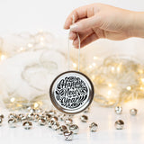 "A hand holds a silver mason jar lid Christmas ornament that says ""Happy New Year"" in black cursive on a white background with black curly queues. In the background of the picture are silver jingle bells and white Christmas lights"