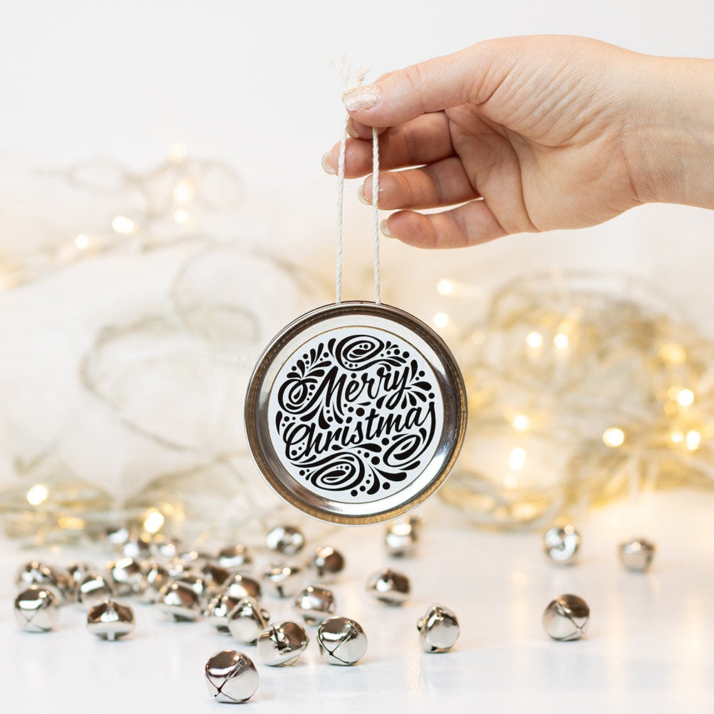 "A hand holds a silver mason jar lid Christmas ornament that says ""Merry Christmas"" in black cursive on a white background with black curly queues. In the background of the picture are silver jingle bells and white Christmas lights"