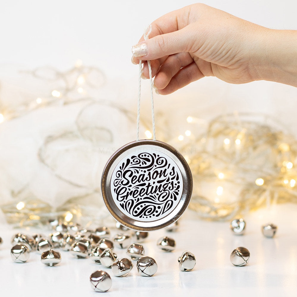 "A hand holds a silver mason jar lid Christmas ornament that says ""Season's Greetings"" in black cursive on a white background with black curly queues. In the background of the picture are silver jingle bells and white Christmas lights"