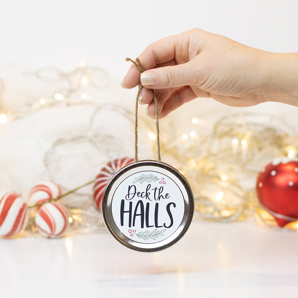 "A hand holds a silver mason jar lid Christmas ornament that says ""Deck the Halls"" in black cursive on a white background with green holly and red berries surrounding it. In that background of the picture are some red and white ornaments and white Christmas lights"