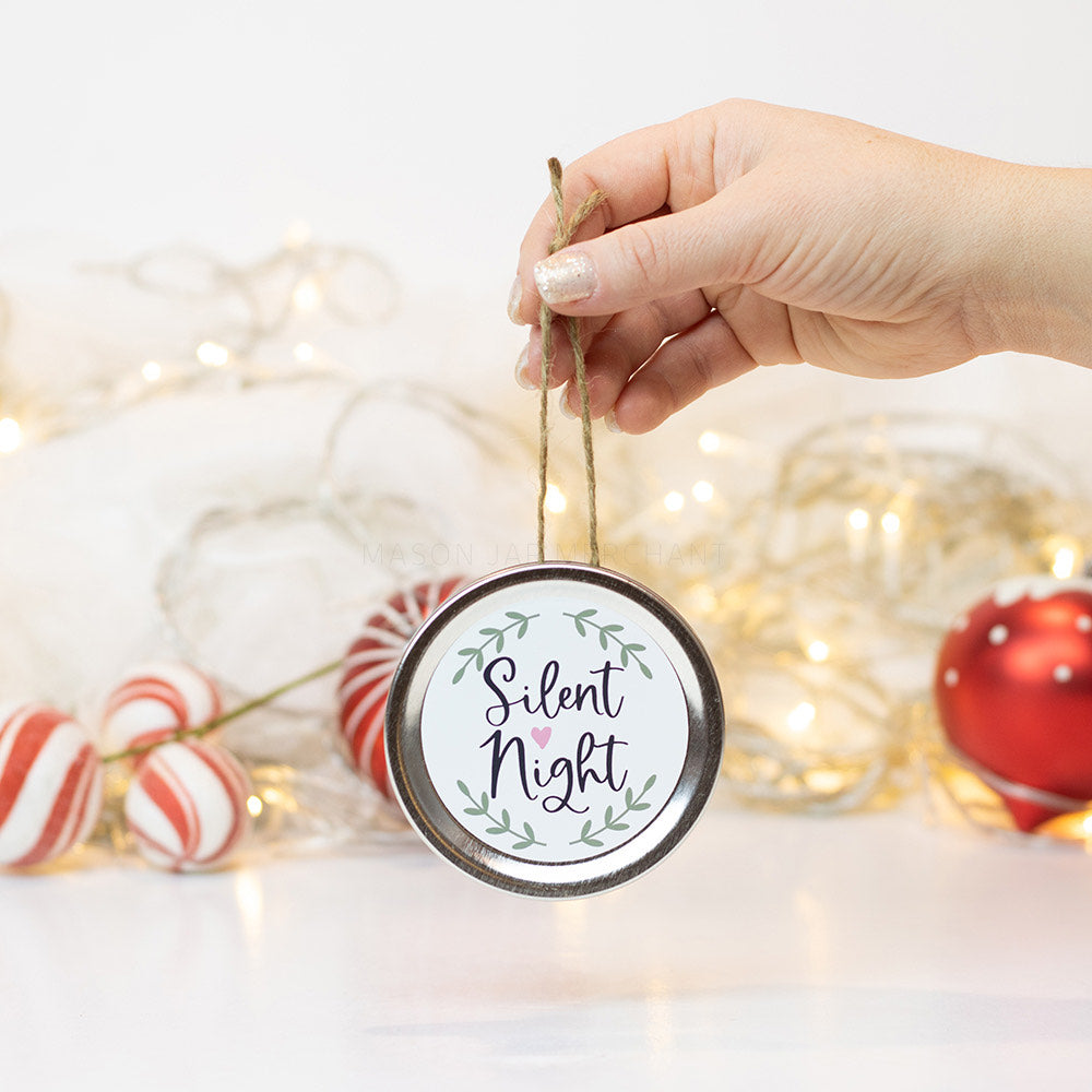 "A hand holds a silver mason jar lid Christmas ornament that says ""Silent night"" in black cursive on a white background with green leaves surrounding it. In that background of the picture are some red and white ornaments and white Christmas lights"