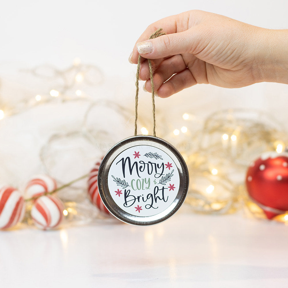 "A hand holds a silver mason jar lid Christmas ornament that says ""Merry Cozy & Bright"" in black and green cursive on a white background with black leaves and red flowers surrounding it. In that background of the picture are some red and white ornaments and white Christmas lights"