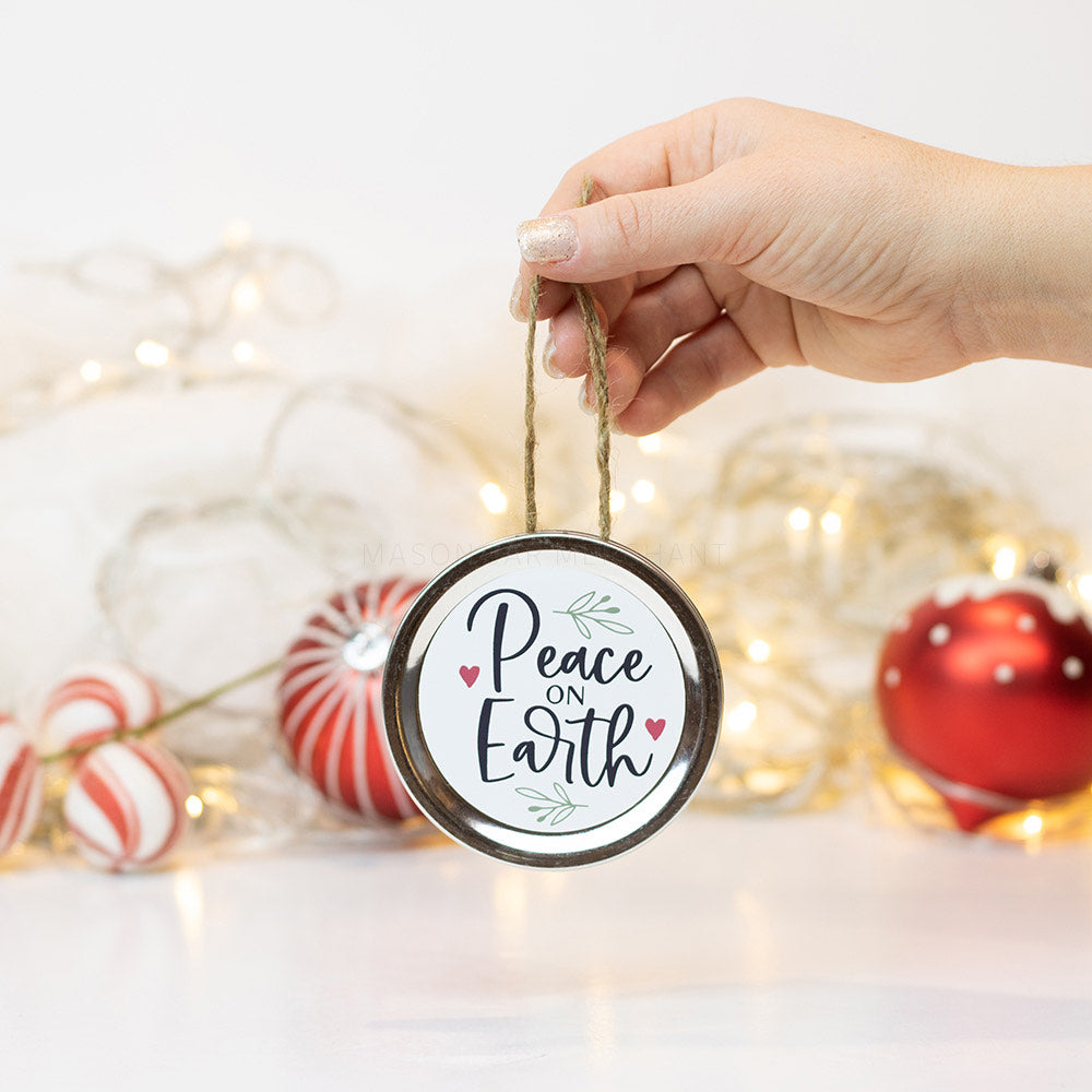 "A hand holds a silver mason jar lid Christmas ornament that says ""Peace on Earth"" in black text on a white background with green leaves and red hearts surrounding it. In that background of the picture are some red and white ornaments and white Christmas lights"