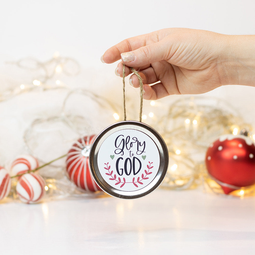 "A hand holds a silver mason jar lid Christmas ornament that says ""Glory to God"" in black cursive on a white background with red leaves surrounding it. In that background of the picture are some red and white ornaments and white Christmas lights"