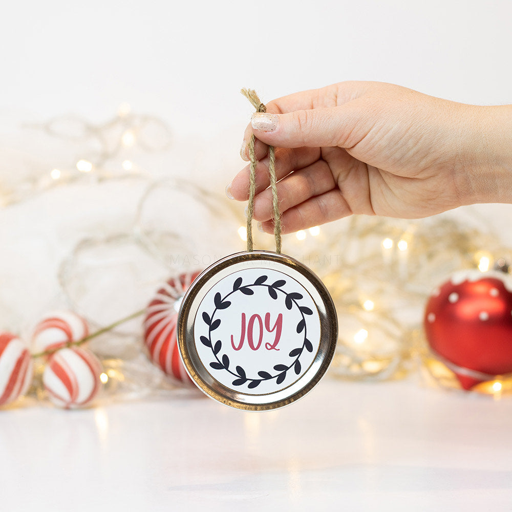 "A hand holds a silver mason jar lid Christmas ornament that says ""Joy"" in red cursive on a white background with black leaves surrounding it. In that background of the picture are some red and white ornaments and white Christmas lights"