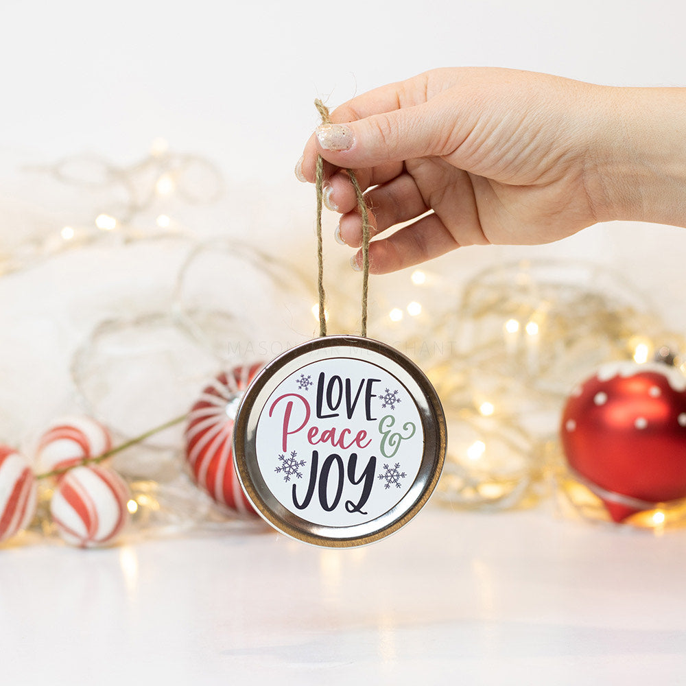 "A hand holds a silver mason jar lid Christmas ornament that says ""Love Peace & Joy"" in black, green and red  cursive on a white background with silver snowflakes surrounding it. In that background of the picture are some red and white ornaments and white Christmas lights"