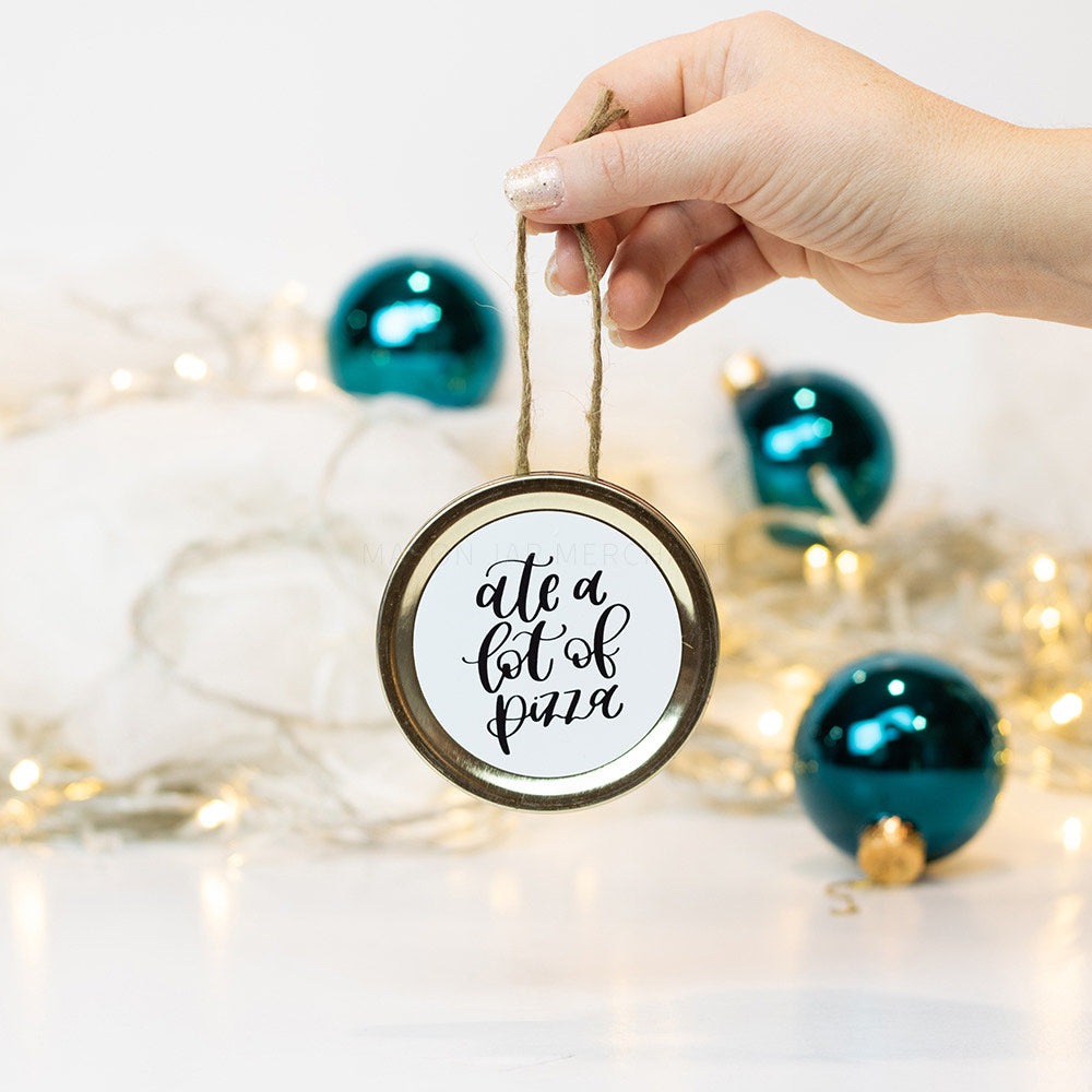 "A hand holds a gold mason jar lid Christmas ornament that says ""ate a lot of pizza"" in black cursive on a white background. In the background of the picture are teal ball ornaments and white Christmas lights"