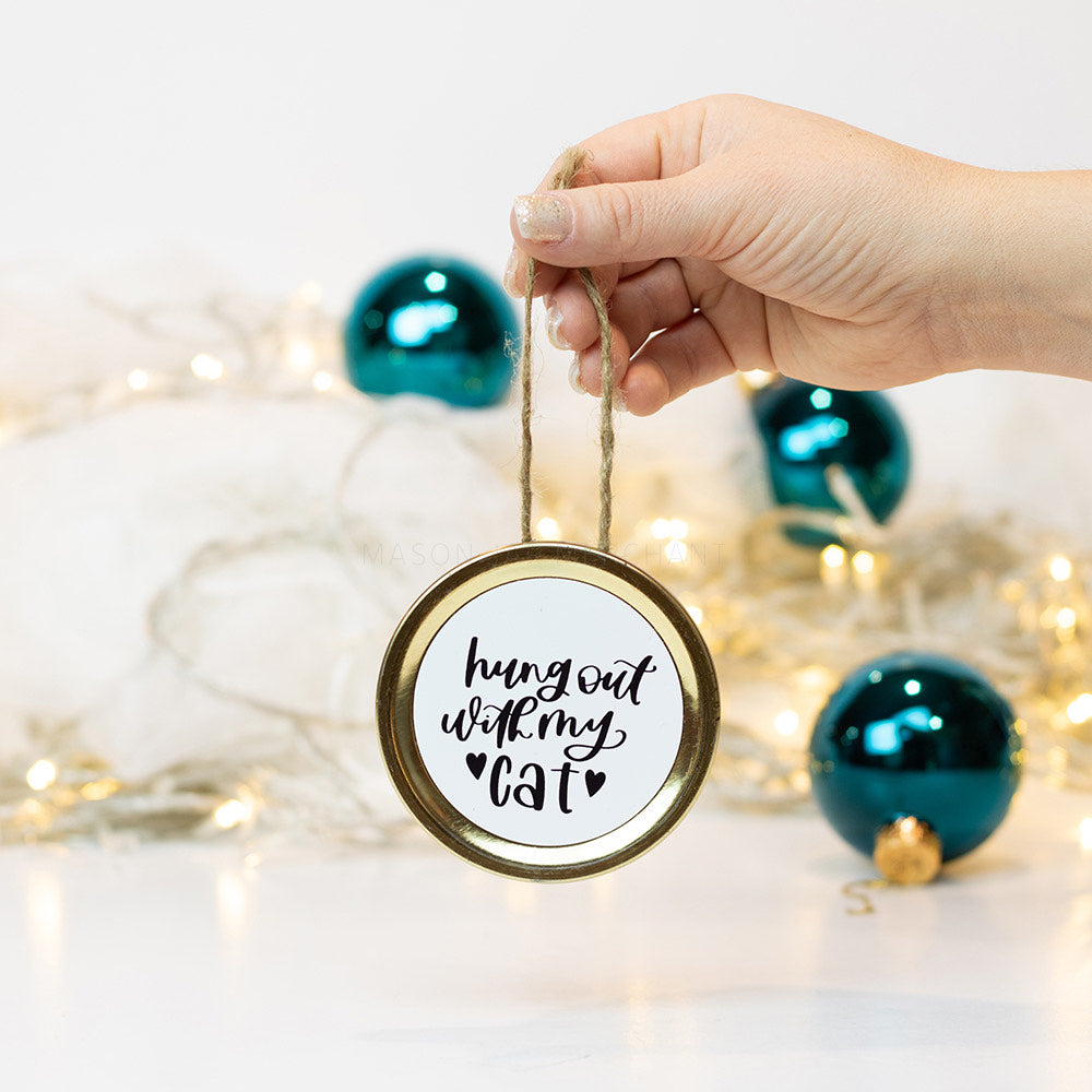 "A hand holds a gold mason jar lid Christmas ornament that says ""hung out with my cat"" in black cursive on a white background. In the background of the picture are teal ball ornaments and white Christmas lights"