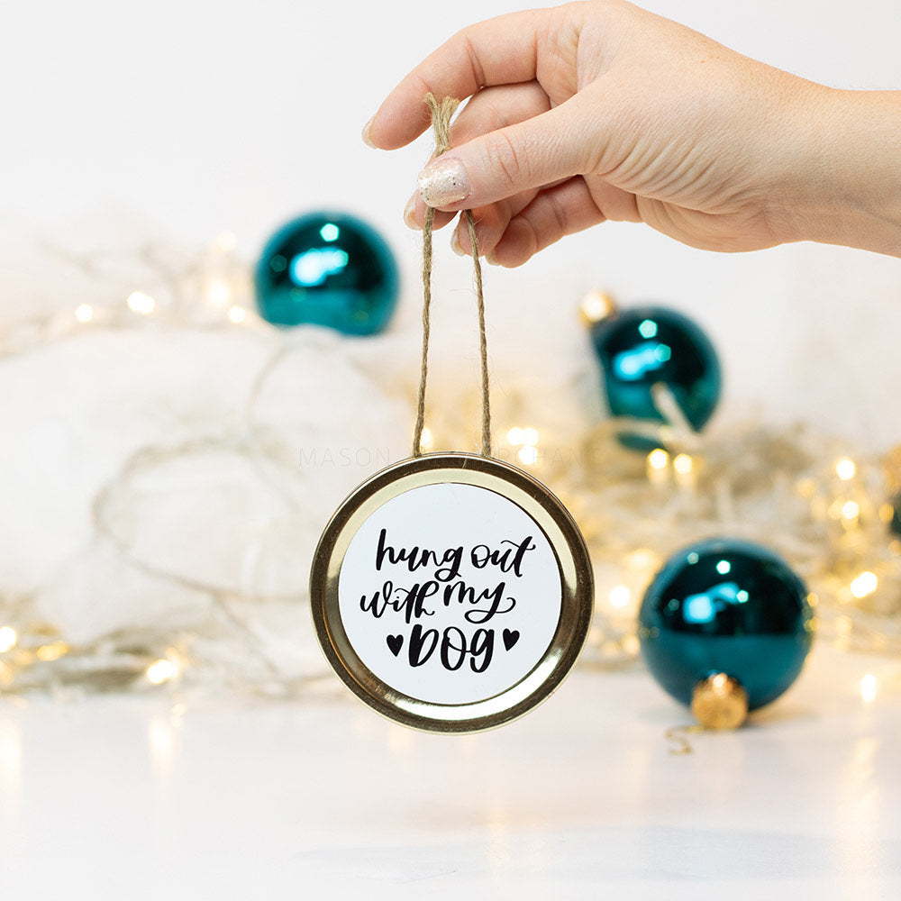"A hand holds a gold mason jar lid Christmas ornament that says ""hung out with my dog"" in black cursive on a white background. In the background of the picture are teal ball ornaments and white Christmas lights"