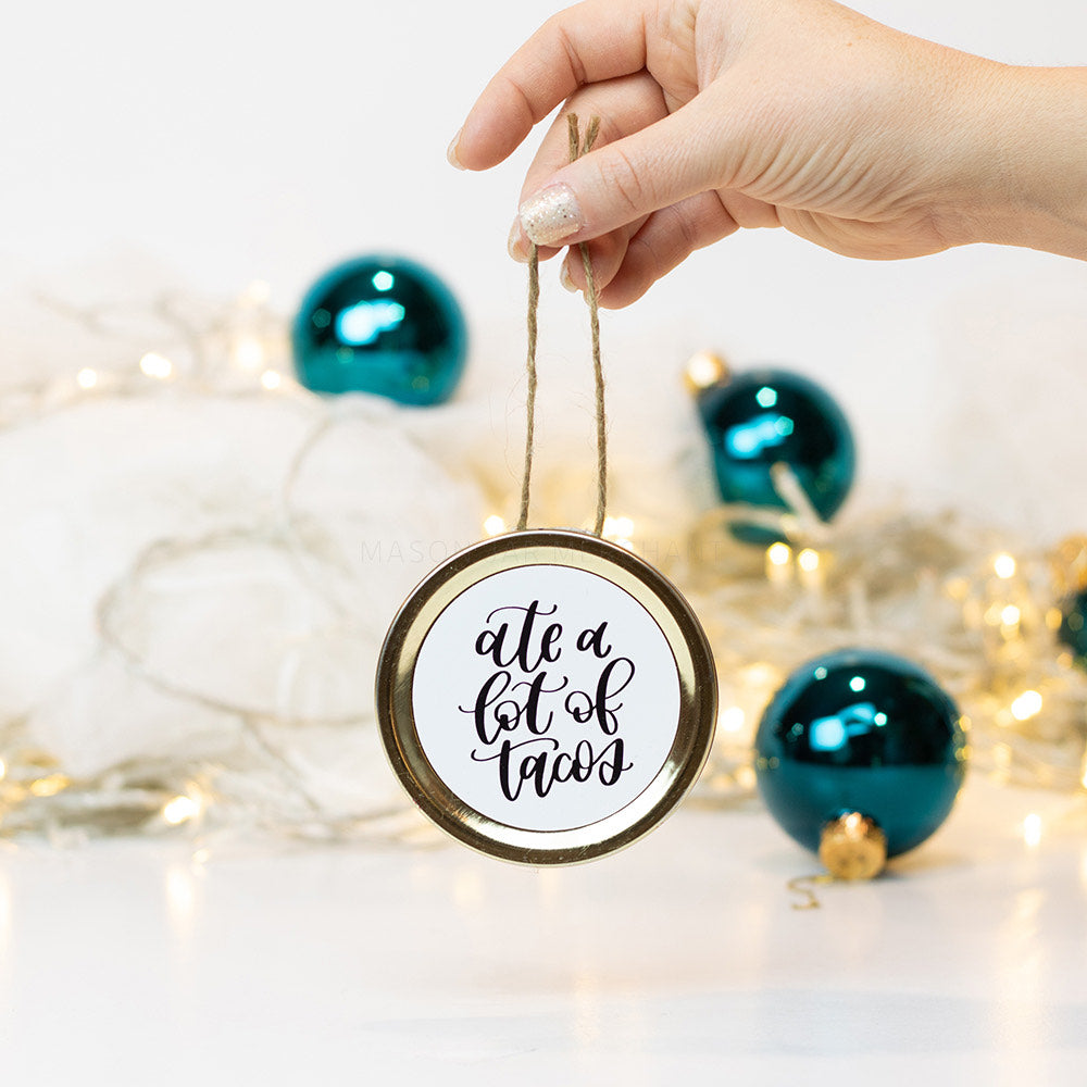 "A hand holds a gold mason jar lid Christmas ornament that says ""ate a lot of tacos"" in black cursive on a white background. In the background of the picture are teal ball ornaments and white Christmas lights"