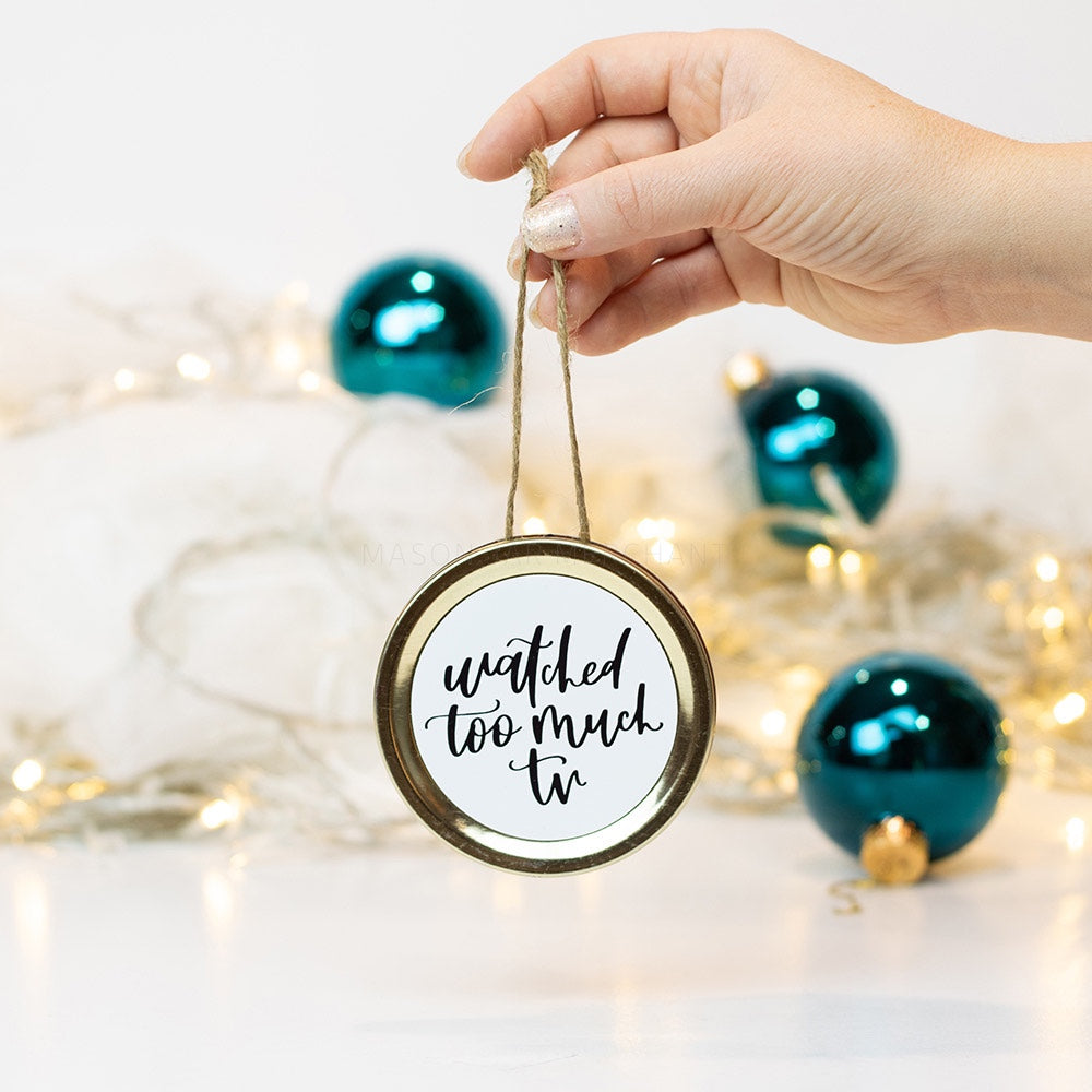 "A hand holds a gold mason jar lid Christmas ornament that says ""watched too much tv"" in black cursive on a white background. In the background of the picture are teal ball ornaments and white Christmas lights"
