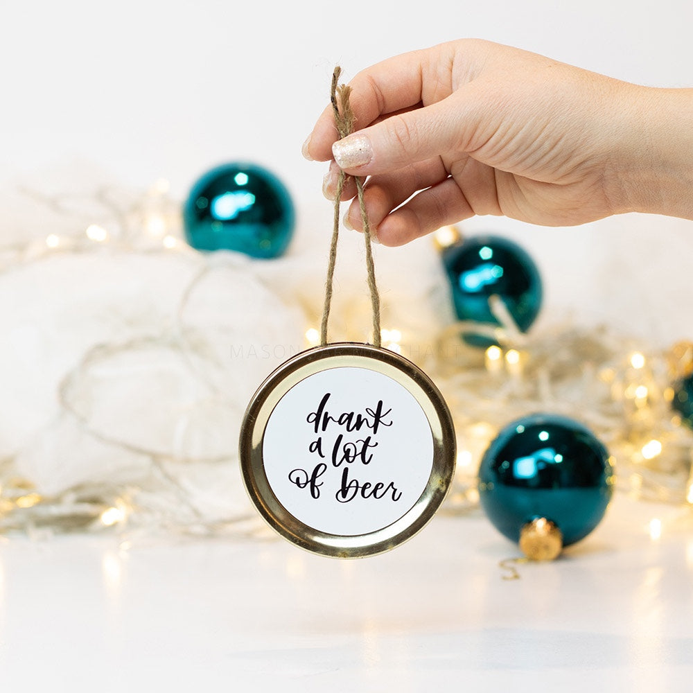 "A hand holds a gold mason jar lid Christmas ornament that says ""drank a lot of beer"" in black cursive on a white background. In the background of the picture are teal ball ornaments and white Christmas lights"