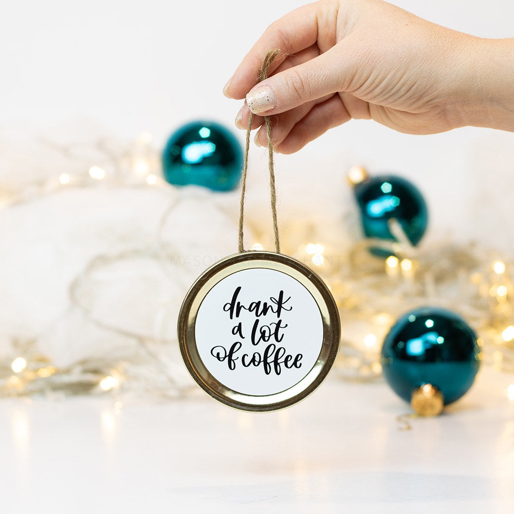 "A hand holds a gold mason jar lid Christmas ornament that says ""drank a lot of coffee"" in black cursive on a white background. In the background of the picture are teal ball ornaments and white Christmas lights"
